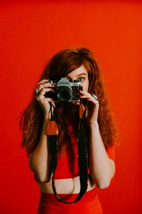 permanent red hair dye uk, woman in red top with long red hair, holding a camera,, against a red background