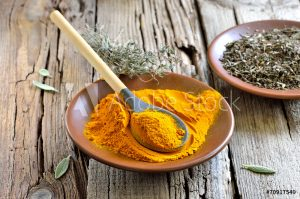 Turmeric henna add in for blondesplate with turmeric powder and wooden spoon
