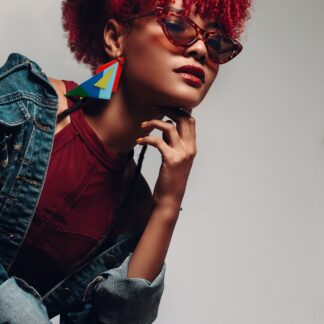 Beautiful woman wearing denim jacket and large statement jewellery and sunglasses, with natural hair dyed red