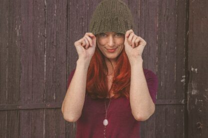 Best red hair dye on long red hair; woman wearing green beanie hat pulled over her upper forehead, with long red auburn hair faling in front off her shoulders