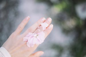 Organic neem is good for your nails too, hands showing off beautiful natural pink naiols with pink petals on fingers