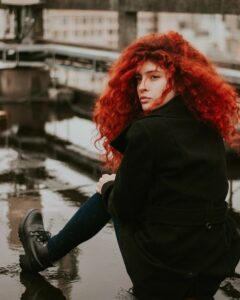 young woman wearing black over coat with long thick wavy red hair