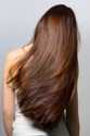 natural hair care, woman in white dress with long brown hair down her back