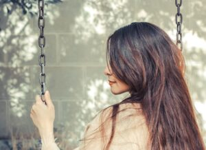 woman with long brown hair sitting on a swing