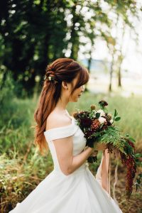 Light auburn hair colour; bride wearing off the shoulder dress with long light auburn hair falling behind her back, holding a bunch of wild flowers