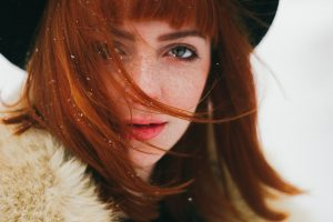 Natural auburn hair colour on woman wearing fur collared coat and black hat