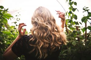 amla hair waves and amla hair curl; picture of woman with her back fgacing the camera, sowing off her long, wavy, blonde hair in the sunshine