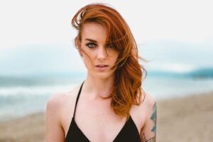 woman with long auburn hair in black strappy dree standing against a beach sea background