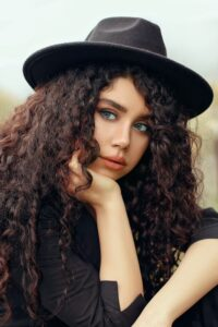 Natural brown hair colouring on beautiful thick long wavy hair on woman dressed in black wearing a black hat