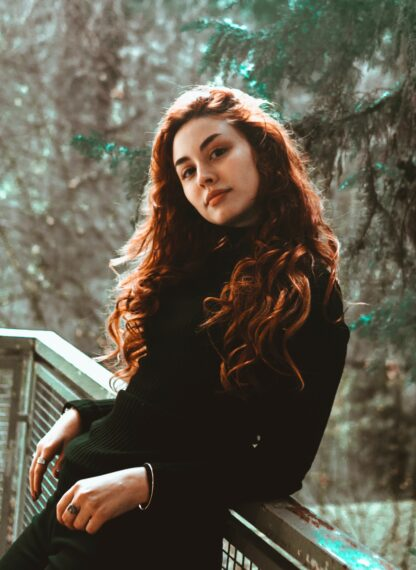with long hair perched against a balcony railnatural auburn brown hair dye on lady