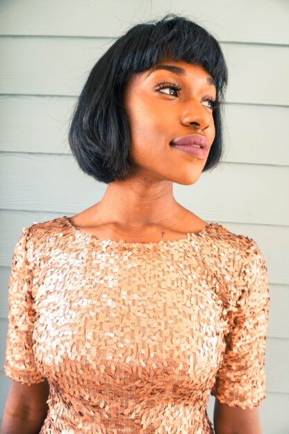 herbal hair colouring with henna indigo; beautiful black woman wearing glittery gold dress, sporting short straight bob haircut