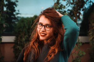 woman wearing glasses with long wavy auburn red natural hair colour, hair dyed