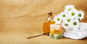 natural cleansers for hair and body, photo of natural soaps alongside a bunch of white flowers and a bottle of cidar vinegar for hair rinsing