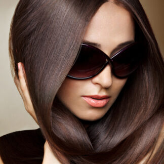 Woman wearing sunglasses with natural glossy dark brown black hair dye