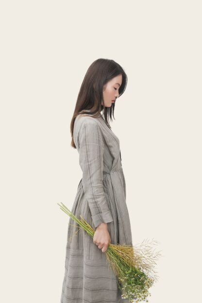 young lady with beautiful sleek strong long hair wearing a lng sleeve long cotton dres holding a bunch of dried flowers