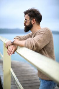man with dark brown black ahir and beard and beige cream jumper standing at a fence and looking out to sea
