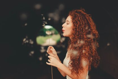 woman with long auburn wavy hair with ppd free auburn henna hair dye, holding a plant and blowing