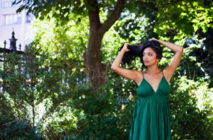 model with strappy green dress and long black hair with indigo natural hair colour
