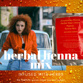 woman with curly ginger hair colour wearing orange short top and jeans standing against a car in an urban area, alongside a packet of Renaissance Henna Herbal Organic Auburn Henna Mix