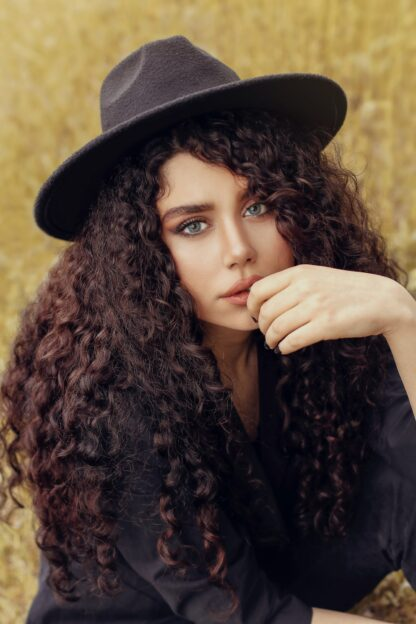 Natural brown permanent hair dye in long curly hair, woman dressed in blakc wearing a dark colour hat