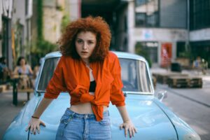 woman with curly ginger hair colour wearing orange short top and jeans standing against a car in an urban area