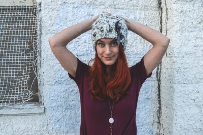 woman with long red hair and white beanie hat sporting natural red hair dye from Morocco
