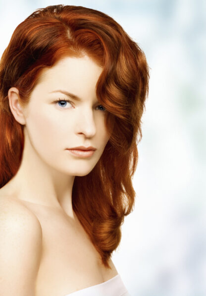 organic henna hair dye on beautiful red head with long wavy hair flowing over one shoulder, wearing a white towel covering upper part of her body