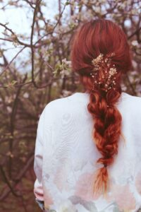 woman with organic henna hair dye on long braided hair, back view of her over her back