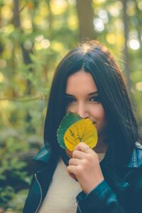 woman with straight short bob dark brown black hair dye holding two leaves up in front of her face