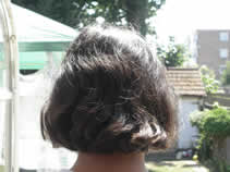 Back of girl's head showing black hair before henna application