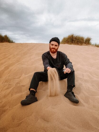 bearded man wearing dark colour beanie hat & jeans ,sitting on beach in relaxed pose with beard na dhair conditioned with mens natural beard oil