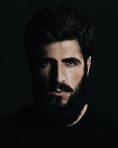 Man with conditioned beard and hair from Mens Natural Beard Oil; bearded dark haired man wearing dark T shirt with a serious gaze