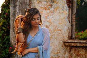 henna hair colour, Renaissance Henna, photo of Asian woman wearing pastel blue long ethnic dress, touching her long brown hair glowing in the sunlight