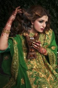 Henna and Dry Hair , Indian Woman in traditional , decorated, green and gold dress, touching her beautiful , long brown hair