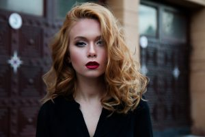 Organic strawberry blonde; woman wearing black with shoulder length, wavy, strawberry blonde colour hair