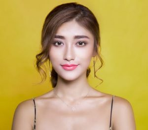 Tumeric Secret Beauty Mix for Glowing Skin, young asian woman with natural looking glowing skin and shiny hair, standing against a full yellow background
