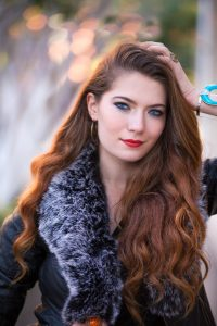 henna with add ins on light brunette hair colour, photo of woman with long soft brown hair wearing a black coat with grey fur collar
