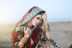 Rajasthani henna; beautiful Indian woman in traditional decorated clothingwith her head covered
