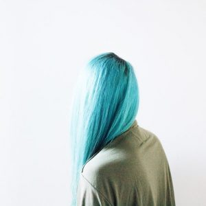 Blonde hair colour to Light blue , long blonde hair turned turqoise blue, lasy with her back to camera, hair over her shoulder