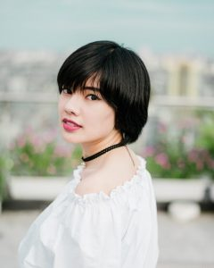 Plant hair dye for short hair will turn hair auburn with henna, and then it will turn your auburn hennaed hair brown through to black hair colour with indigo; woman in white top wearing a black choker, with short black hair.