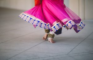 Henna on your feet : picture of Indian lady in long, swirly pink skirt, revealing decorated feet