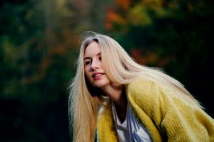 restoring bleached hair is easy with natural  hair care products like cassia obovata; woman wearing yellow cardigan leaning forwards with long blonde hair