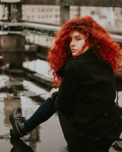 pure henna natural hair dye, red head girl with vibrant thick red wavy curly hair sitting on steps on a rainy day