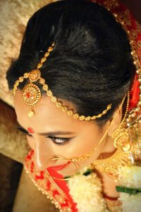 Black Natural Hair Colour close up of Beautiful Asian Woman wearing bridal make up and gold hair jewellery