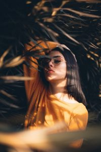 best natural hair dye,, woman in yellow top standing under a tree,touching her long dark brown hair