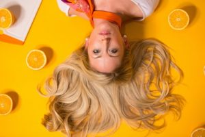 Natural Blonde Highlights botanical hair conditioner, lady with long blonde hair spread out around her, lying down., against a yellow orange background