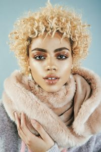 Short Blonde Afro Caribbean Hair on Beautiful Woam Wearing Fur Collared Coat