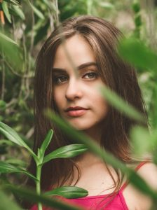 Natural beauty products, plant based, Renaissance Henn, picture of young woman in a forest, with ;eaves and plants around and in front of her face