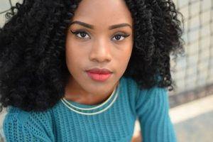 Henna and Perms,, picture of young beautiful afro caribbean lady with shoulder length permed ahir, wearing crew neck blue ribbed jumper