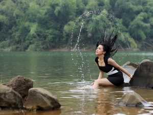 safest hair dye brand is freedom from,; pictore of woman splashing water in a lake